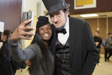 A man dressed as Abe Lincoln poses with a student for a photo.