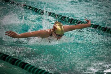 A student races in a swimming competition.