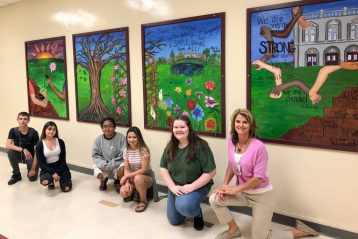 Students pose in front of mural.