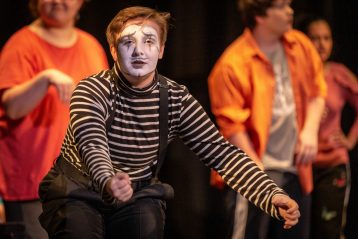 A mime gentures at an audience.